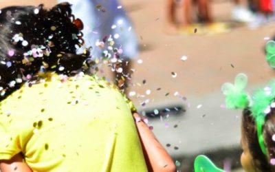 Foto de duas crianças de costas, brincando com confetes.