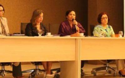 Foto com pessoas sentadas de traz de uma mesa em cima de um palco, uma mulher está falando ao microfone.