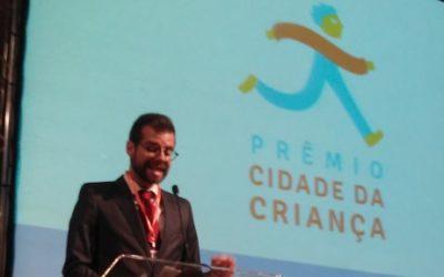 Foto de um homem em um palco em frente ao microfone, ao fundo tem um telão escrito: Prêmio cidade da criança.