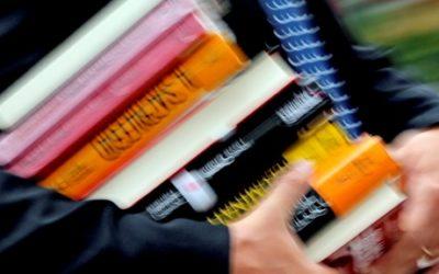 Foto com uma pessoa segurando vários livros.