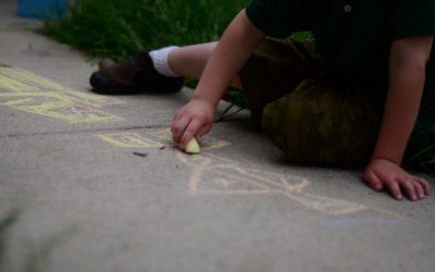 Foto de uma criança desenhando em um chão com um giz.