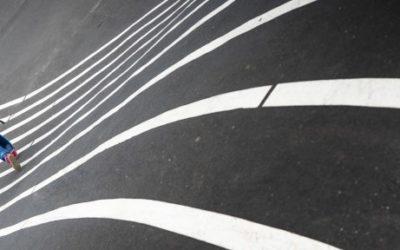 Foto de um garoto de mochila andando sobre linhas brancas.