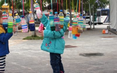 Foto de duas crianças segurando garrafas que estão penduradas em uma praça.