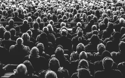 Foto em preto e branco mostra várias pessoas sentadas em auditório