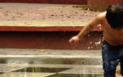 Foto de um garoto brincando no chafariz da praça.