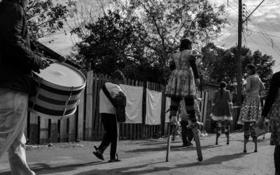 Foto de pessoas em manifestação na rua, com tambores e pernas de pau