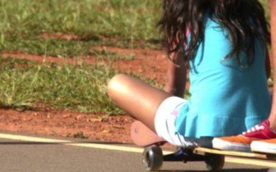 Foto de duas crianças em cima de um skate, uma está em pé o a outra sentada na ponta.