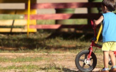 Foto de um garoto segurando uma bicicleta.