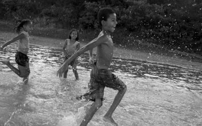 Foto em preto e branco de três crianças brincando no rio