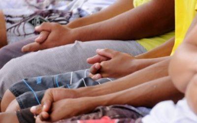 Foto de crianças sentadas em cadeiras formando uma fileira.