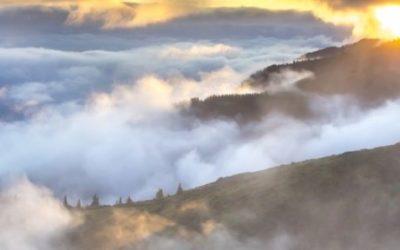 Foto do topo de uma montanha, acima das nuvens.