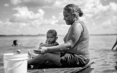 Foto em preto e branco de mulher e criança sentadas à beira do rio