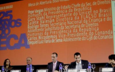 Foto com seis pessoas em cima de um palco, eles estão sentados de traz de uma mesa.