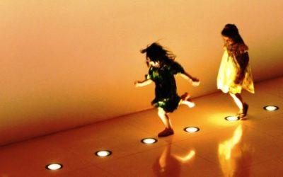 Foto de duas crianças brincando com lâmpadas que estão presas ao chão.