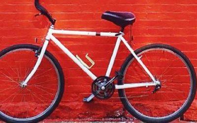 Imagem de uma bicicleta branca encostada em uma parede pintada de vermelho.
