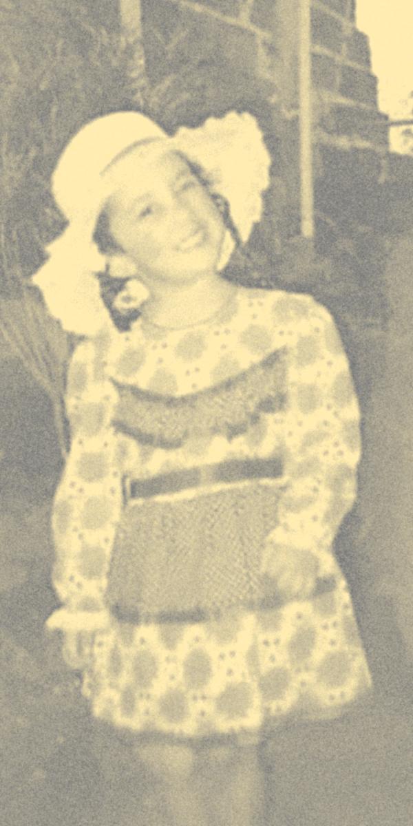 Foto de Camila na infância, vestida com chapéu e roupas de festa junina