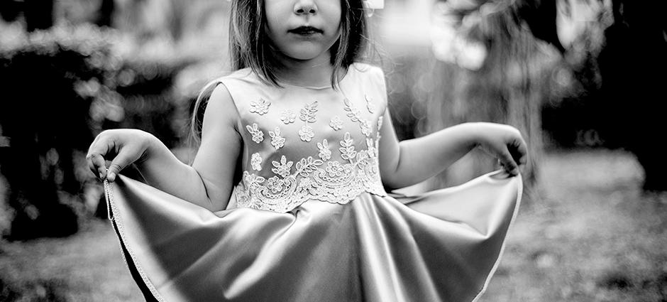 Foto preto e branca de uma menina se cumprimentando com seu vestido.