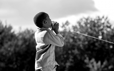 Foto em preto e branco de criança falando em telefone de brinquedo, feito com lata e barbante