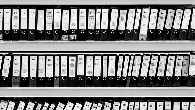 Foto em preto e branco de uma série de pastas de arquivos em prateleira