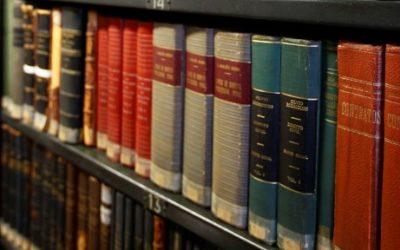 Imagem de livros organizados em prateleiras em uma biblioteca.