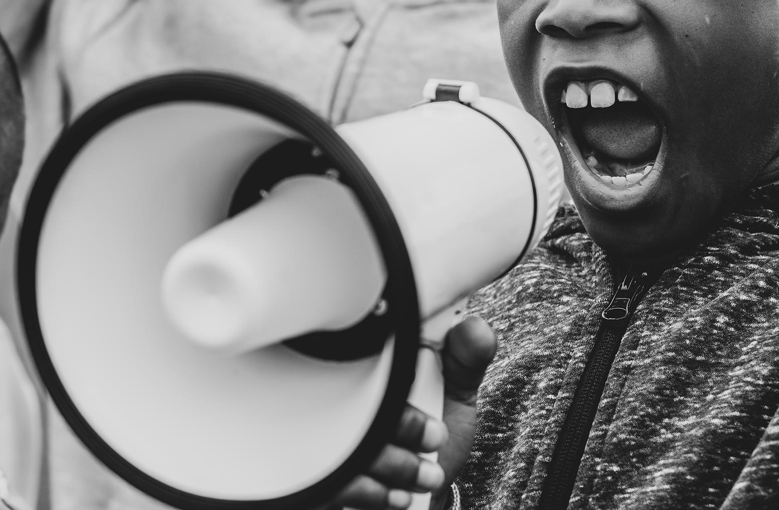 Foto em preto e branco de criança falando em megafone