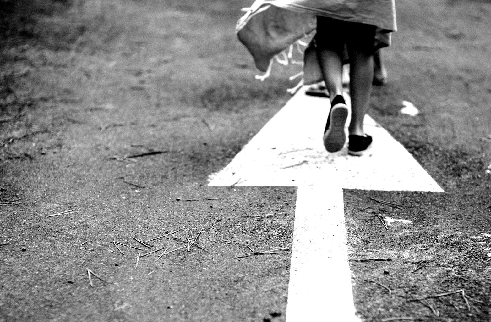 Foto em preto e branco de pés de criança andando sobre seta pintada no chão.