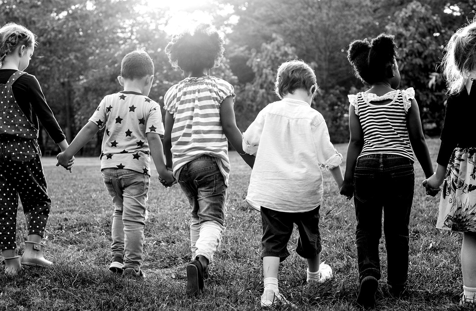 Foto de seis crianças de costas com as mãos dadas.