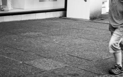 Foto preto e branca de um garoto brincando a beira da calçada com um barquinho de papel.
