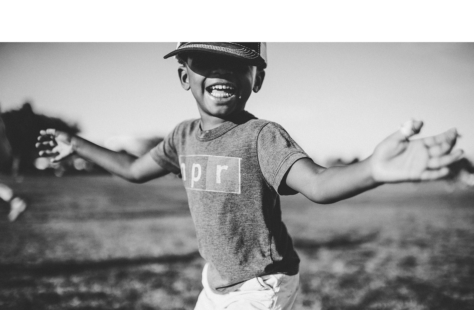Foto em preto e branco de criança de boné sorrindo, com os braços abertos