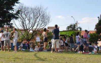 Foto com pessoas em uma quadra de vôlei ao céu aberto.