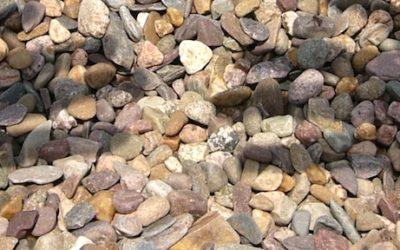 Imagem da sobra de duas mão refletidas em um chão de inúmeras pedras.