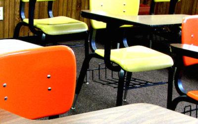 Imagem de carteiras de uma escola.