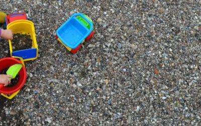 Imagem de uma vista superior de uma criança brincando ao chão com uma pá e um balde de plástico.