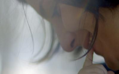 Foto de uma mulher sorrindo, enquanto um bebê toca em seu rosto.