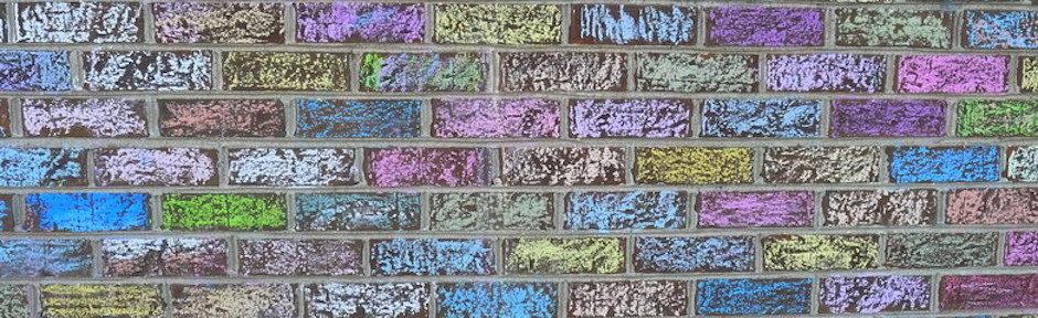 Foto de uma parede de tijolos pitadas com giz, cada tijolo tem uma cor diferente.