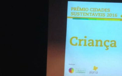 """Foto de um telão com uma imagem que descreve: """"Prêmio cidades sustentável 2016. Criança""""."""