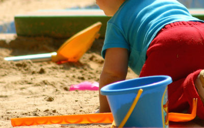 Imagem de uma criança de costas agachada brincando em um chão de areia.