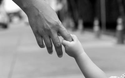 Foto em preto e branco de adulto segurando mão de criança