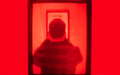 Foto de uma pessoa de costas em uma sala toda vermelha.