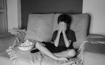 Foto em preto e branco de criança cobrindo os olhos enquanto vê televisão