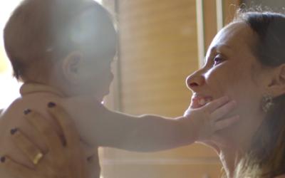 Imagem de um bebê com as mãos no rosto de sua mãe.