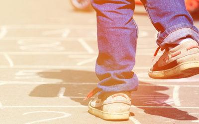 Imagem dos pés de uma criança de costas brincando de amarelinha desenhada ao chão.