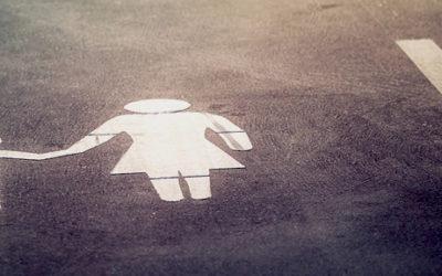 Foto de uma vaga de estacionamento, pintada ao chão um pictograma de uma mulher segurando a mão de uma criança.