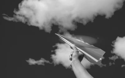 Foto em preto e branco de aviãozinho de papel