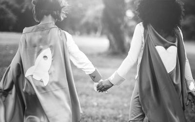 Foto em preto e branco de duas meninas de costas, com capas de super-heroínas