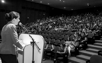 Foto do evento mostra palestrante de costas e auditório cheio