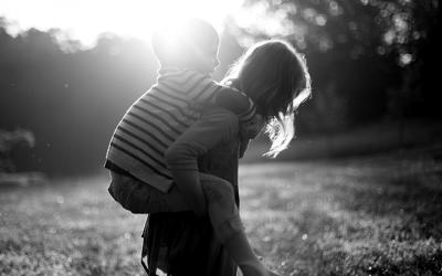 Foto em preto e branco de criança sendo carregada nas costas, de cavalinho