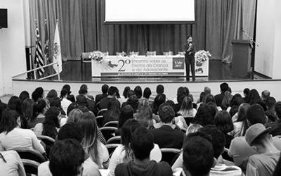 foto em preto e branco  ministrada pela advogada do projeto Prioridade Absoluta, Thais Dantas no 2° encontro sobre o direito da Criança e do Adolescente, no palco em frente a mesa.