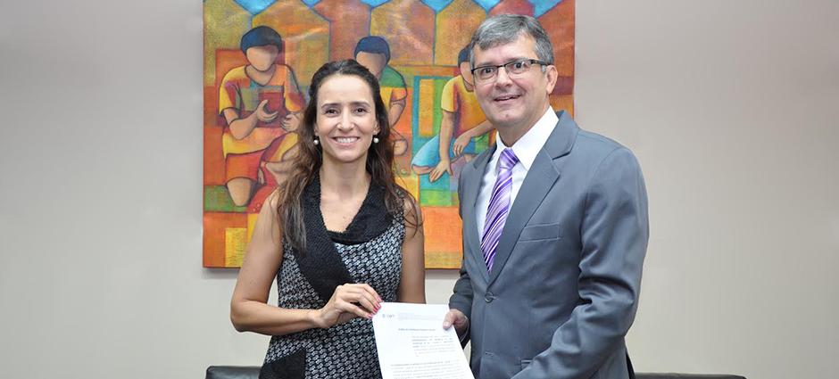 Foto mostrando a diretora de Advocacy do Alana, Isabella Henriques, ao lado do juiz Renato Scussel, coordenador da CIJ/TJDFT. Ambos seguram o documento que sela a parceria entre Alana e TJDFT.