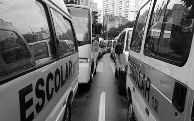 Foto em preto e branco de duas peruas escolares no transito